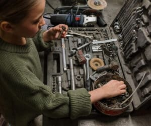 Canva Boy in Green Sweater Holding Gray Metal Tool 300x250